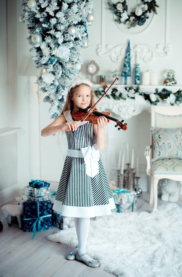 Moça bonito com violinl na sala da decoração do Natal fotografia de stock royalty free