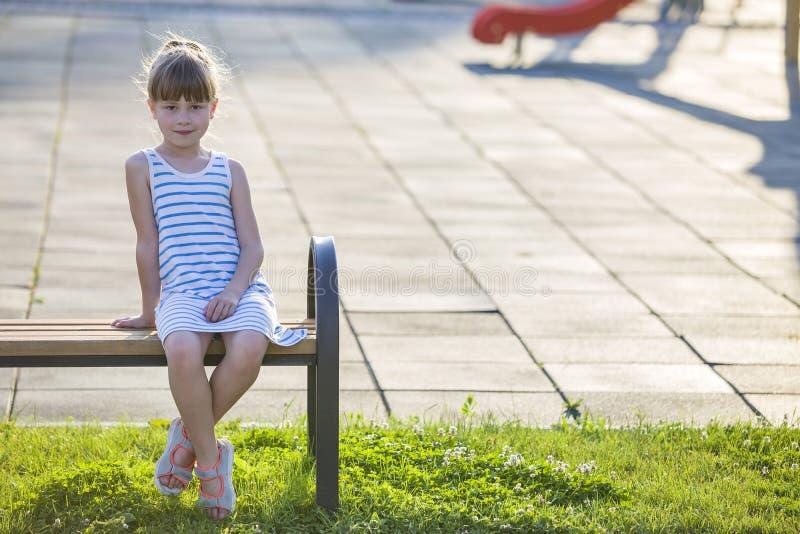 Moça bonito de sorriso que senta-se apenas fora no banco no dia de verão ensolarado foto de stock royalty free