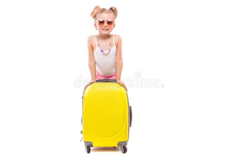 A moça bonito na camisa branca, o short cor-de-rosa e os óculos de sol estão perto da mala de viagem amarela foto de stock royalty free