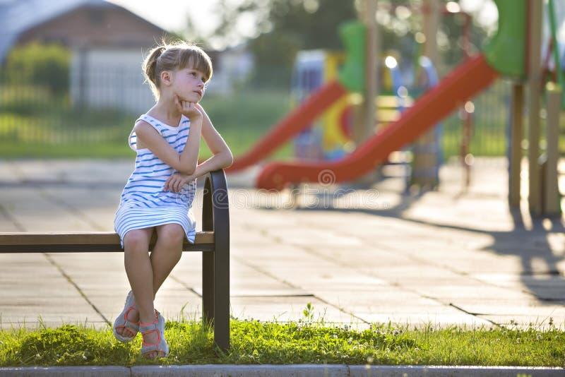 Moça bonito no vestido curto que senta-se apenas fora no banco do campo de jogos no dia de verão ensolarado foto de stock
