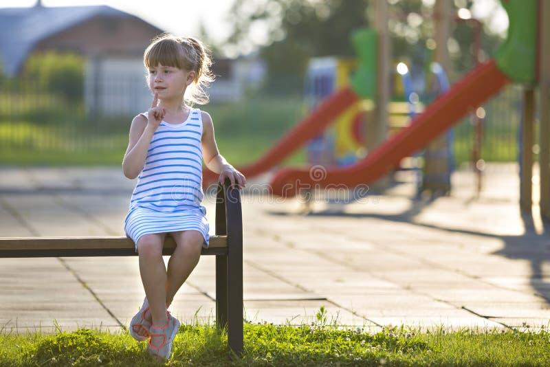 Moça bonito no vestido curto que senta-se apenas fora no banco do campo de jogos no dia de verão ensolarado fotografia de stock royalty free