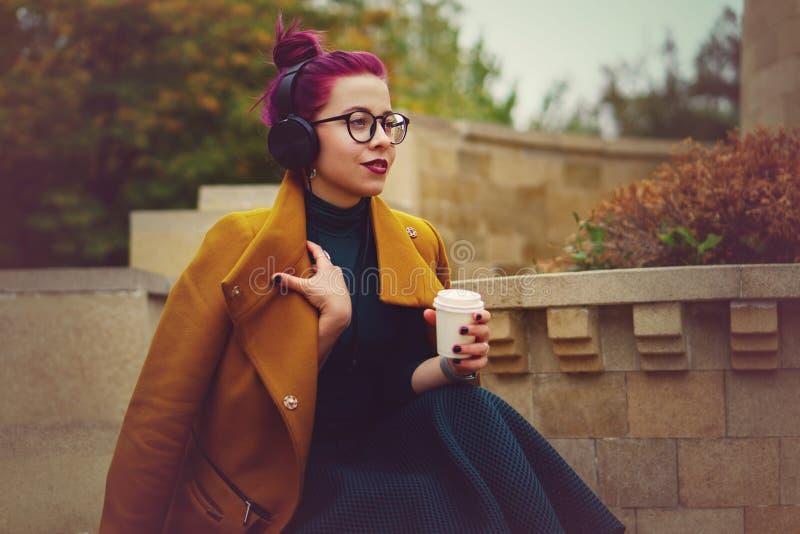 Moça bonito que escuta a música em fones de ouvido no parque do outono A mulher está guardando o copo de papel com bebida quente  fotografia de stock