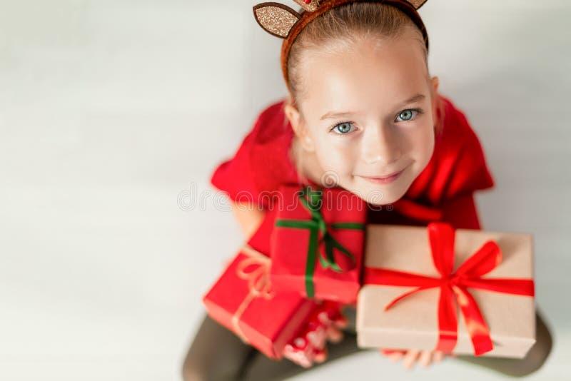 Moça bonito que guarda presentes de Natal, sorrindo e olhando a câmera Criança feliz no tempo do Natal que senta-se no assoalho foto de stock
