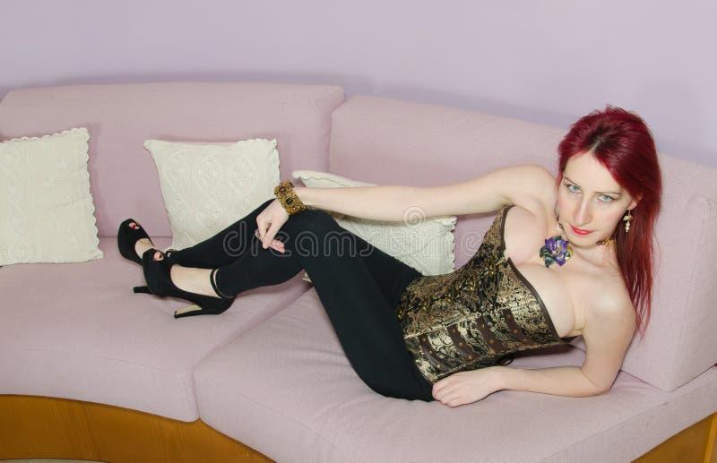 Moça bonito que relaxa no sofá fotos de stock