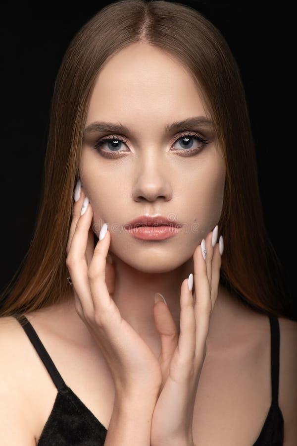 A moça bonito toca levemente em suas mãos à cara com um tratamento de mãos profissional fotografia de stock royalty free