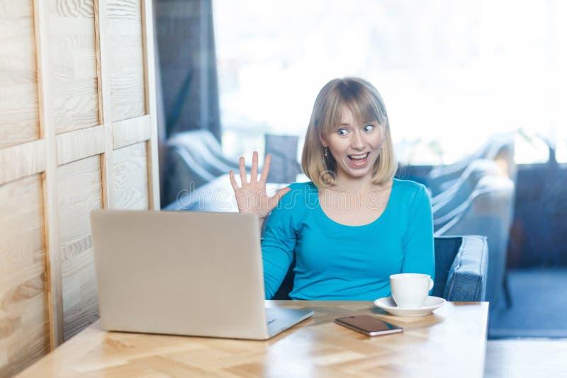 A moça chocada com cabelo louro da mulher de negócios na blusa azul está sentando-se no café e está cumprimentando-se um trabalha imagens de stock royalty free