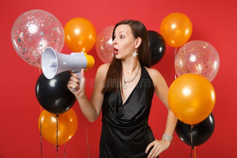 Moça chocada em pouca comemoração preta do vestido, olhando de lado, guardando o megafone em balões de ar vermelhos do fundo imagem de stock