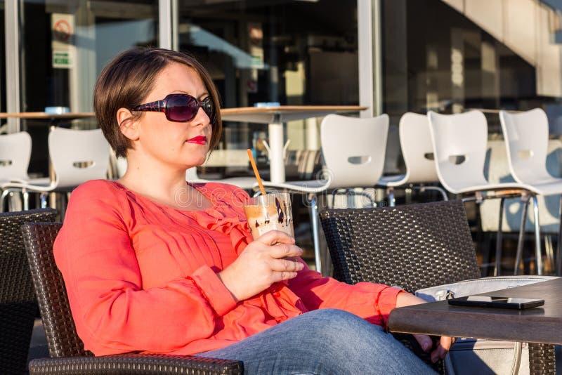 Moça com óculos de sol que bebe o café e que aprecia Sunny Day Outside bonito foto de stock