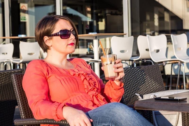 Moça com óculos de sol que bebe o café e que aprecia Sunny Day Outside bonito imagem de stock