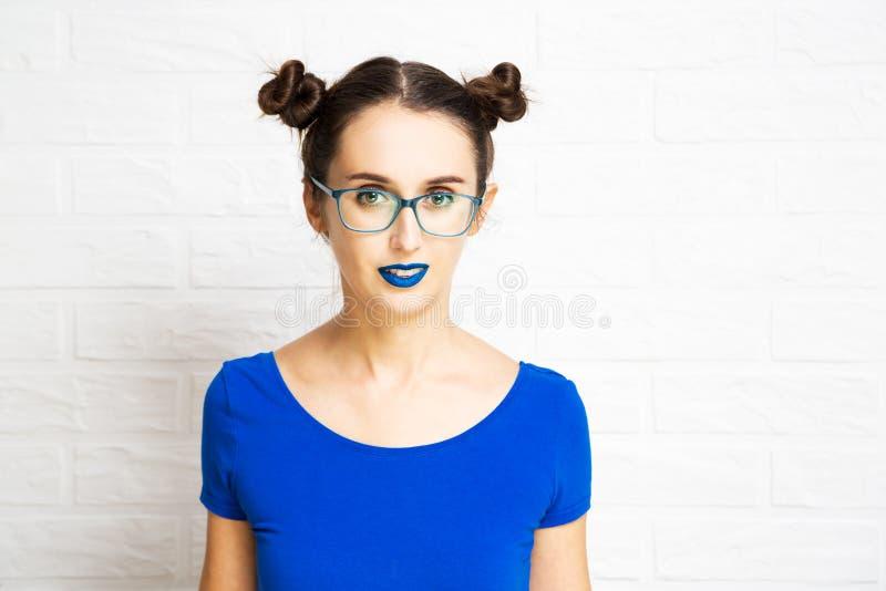Moça com bordos azuis e dois bolos do cabelo foto de stock royalty free