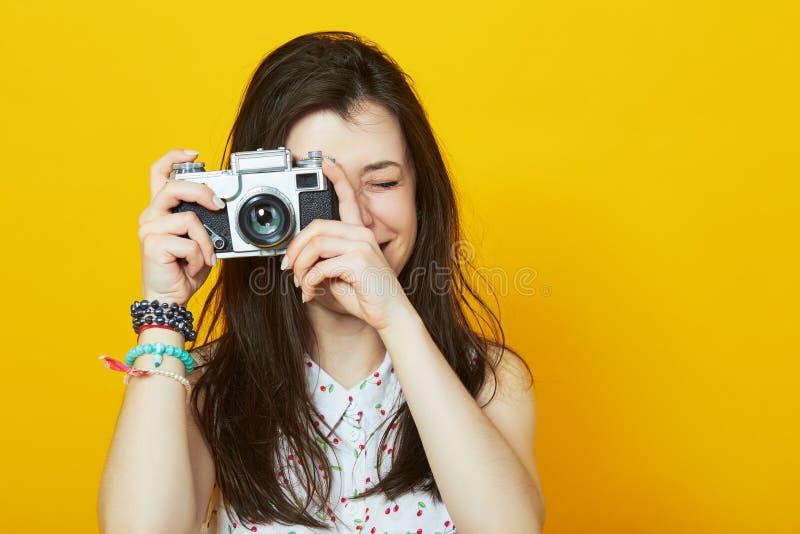 Moça com câmera retro que sorri contra uma parede amarela imagens de stock royalty free