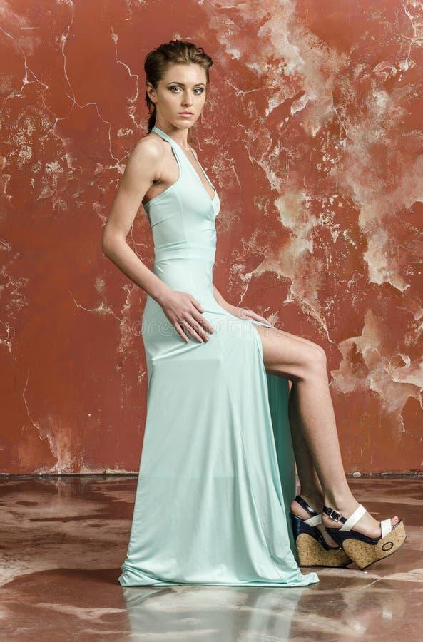 Moça com cabelo bonito em um vestido azul longo e em sandálias da plataforma fotografia de stock royalty free