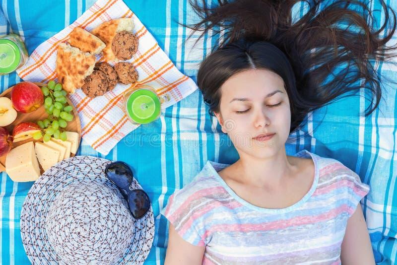 A moça com cabelo escuro longo está encontrando-se em uma manta em um piquenique em um dia de verão - férias de verão e conceito  foto de stock