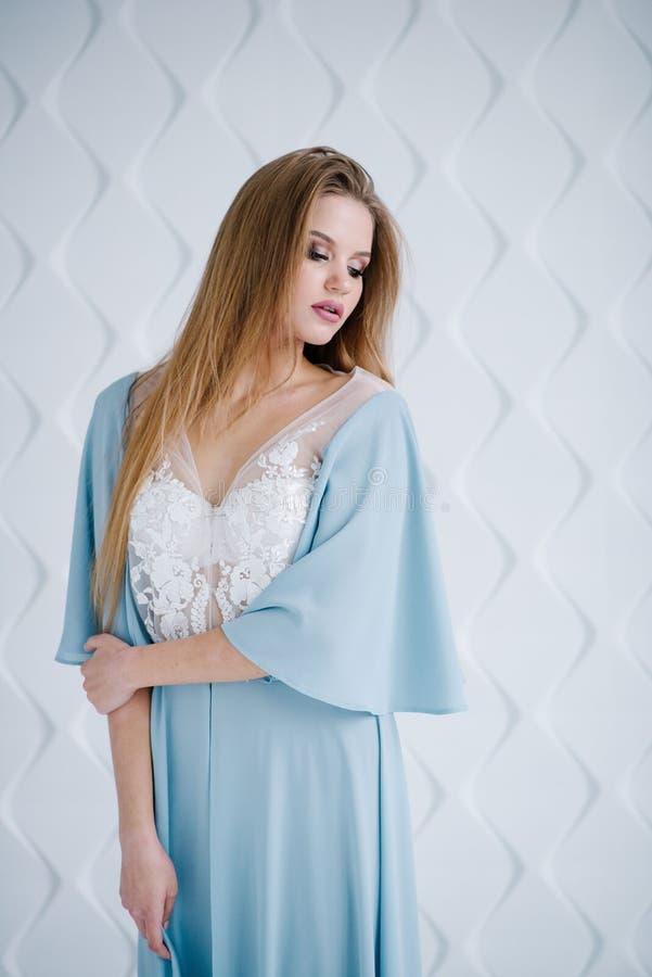 A moça com cabelo longo e a forma compõem, no vestido azul bonito imagens de stock royalty free