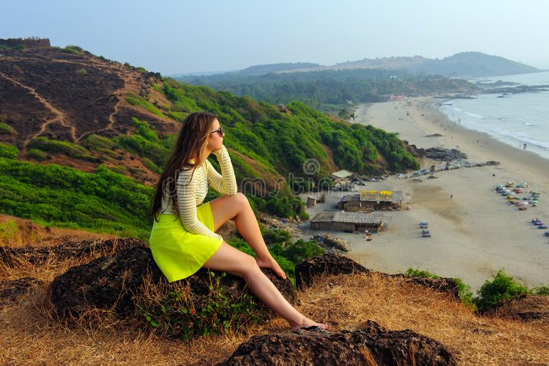 A moça com cabelo longo no vestido amarelo senta-se na rocha sobre um monte verde que negligencia a praia e o mar abaixo imagens de stock