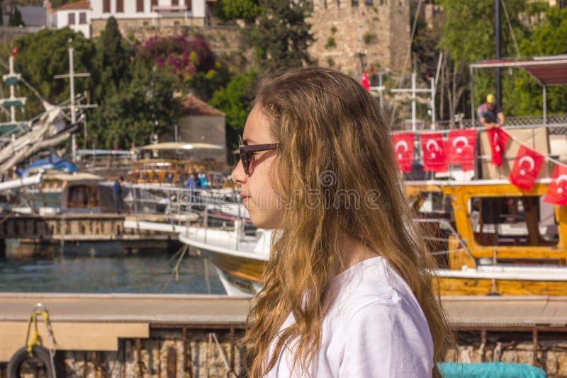 A moça com cabelo longo senta-se no cais no porto do iate e em olhares no mar azul foto de stock