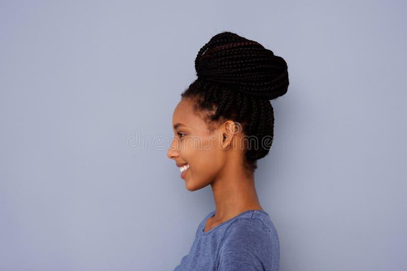 Moça com cabelo trançado em um bolo pela parede cinzenta foto de stock