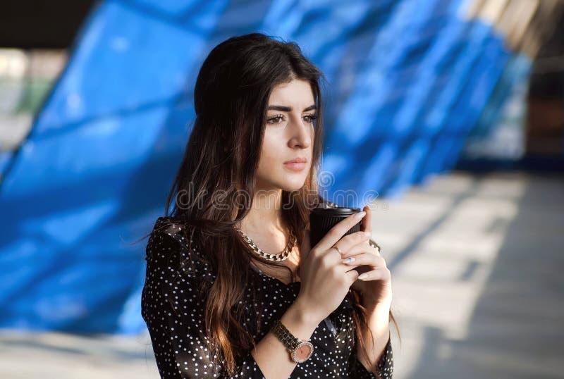 Moça com café de pensamento e bebendo longo do cabelo na rua urbana da cidade Mulher séria com copo descartável fotografia de stock