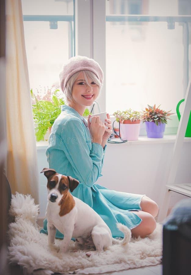 Moça com copo e cão em casa foto de stock royalty free