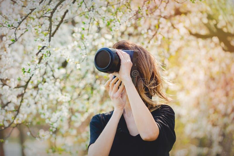 Moça com estada da câmera perto de uma árvore de florescência fotos de stock