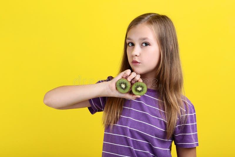Moça com fruto de quivi imagens de stock