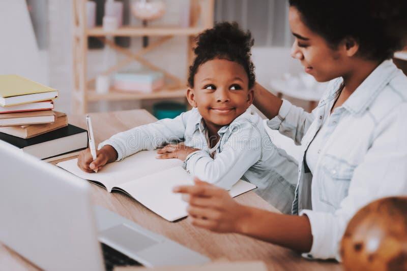 Moça com mãe e portátil para lições imagem de stock royalty free