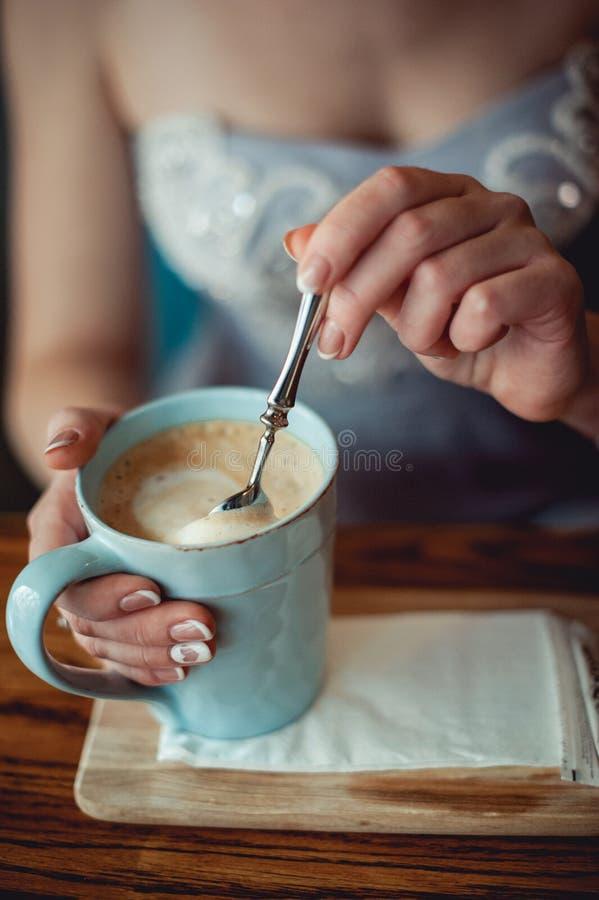 Moça com mãos agradáveis com o tratamento de mãos francês branco que mistura um coffe no copo azul do vintage foto de stock