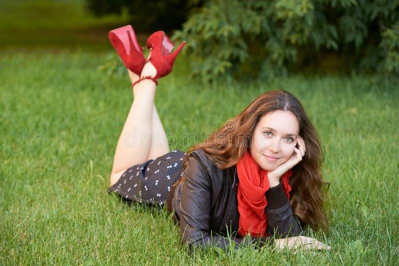 Moça com o lenço vermelho que encontra-se na grama verde imagem de stock
