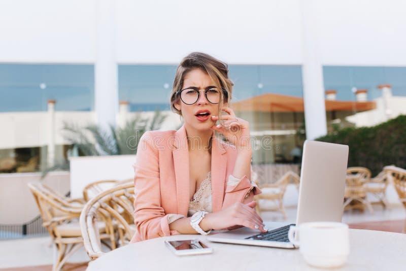 Moça com o portátil no café da rua com olhar facial desagradado da expressão, irritada ou descontentado Vestir ? moda fotos de stock