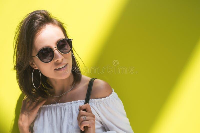 Moça com os óculos de sol sobre a vista verde do fundo imagem de stock