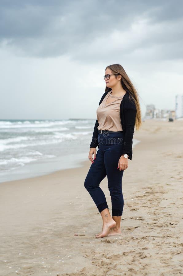 Moça com os vidros que levantam na praia em um dia nebuloso fotografia de stock royalty free