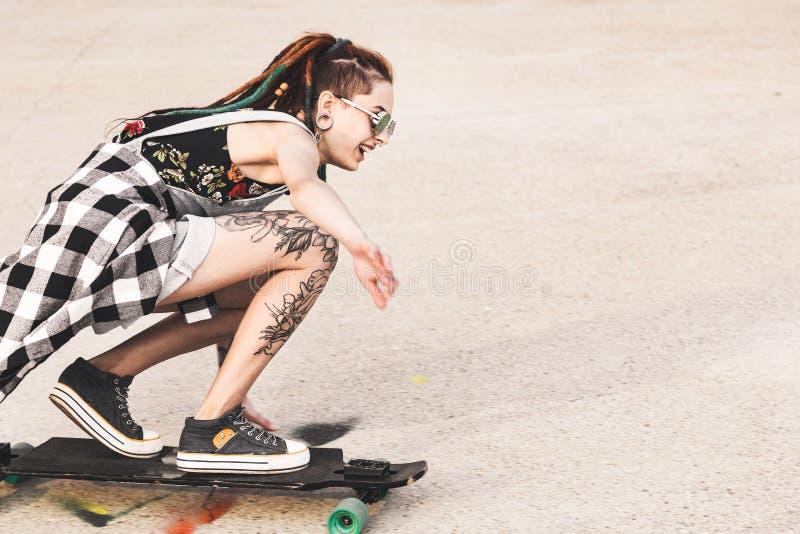 Moça com passeios da tatuagem em um longboard foto de stock
