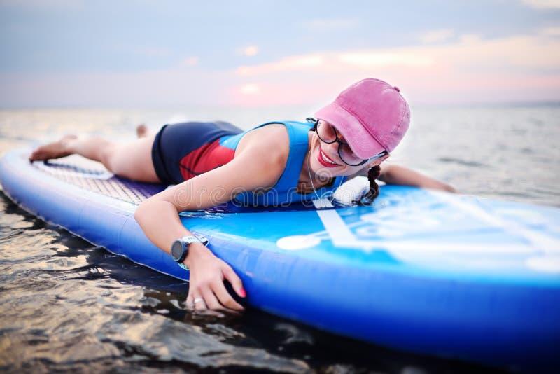 Moça com placa do sup no fundo do mar e do por do sol fotos de stock