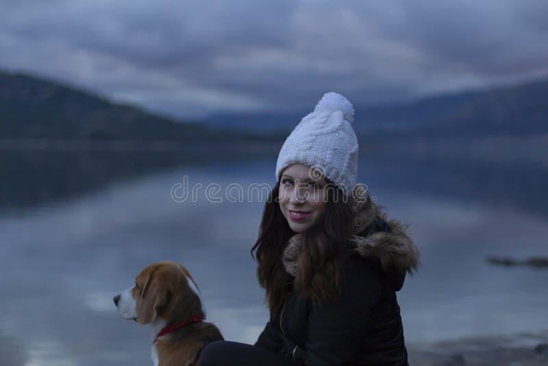 Moça com seu cão por um lago imagens de stock
