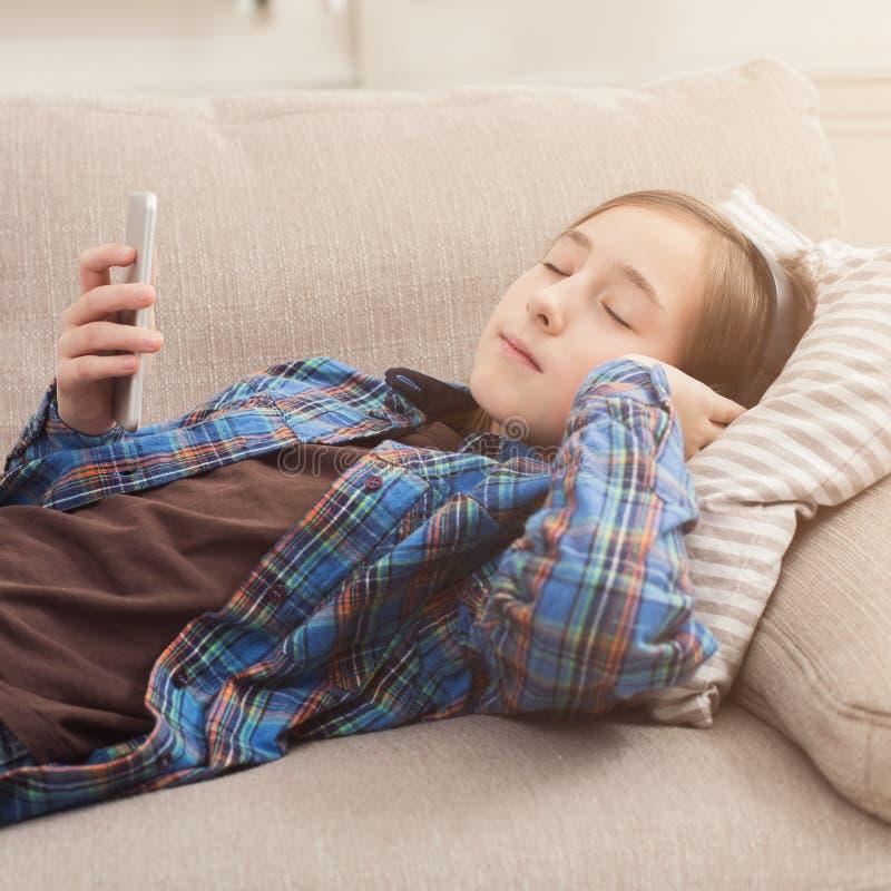 Moça com smartphone em casa imagem de stock