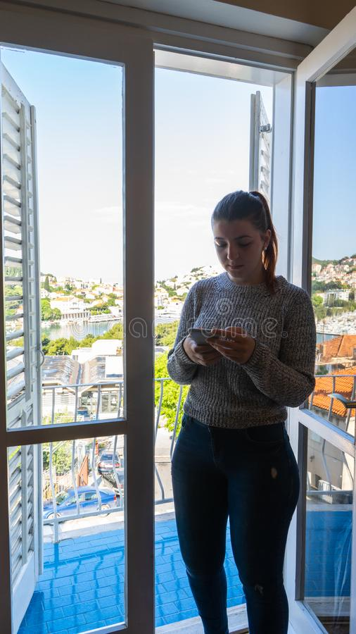 Moça com telefone esperto em uma sala com balcão Mulher principal vermelha com a camisa longa cinzenta Cortinas e porta de madeir fotografia de stock royalty free