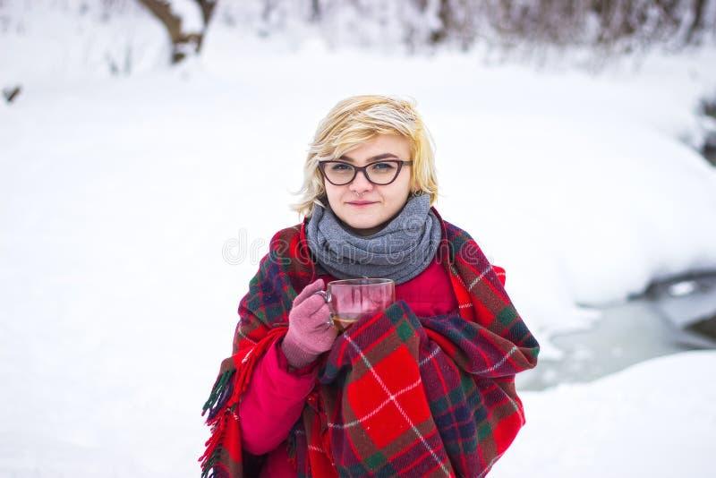 Moça com um copo do inverno no parque, cookware do acampamento imagens de stock royalty free