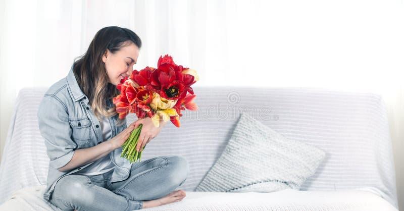 Moça com um ramalhete das tulipas na sala de visitas imagens de stock