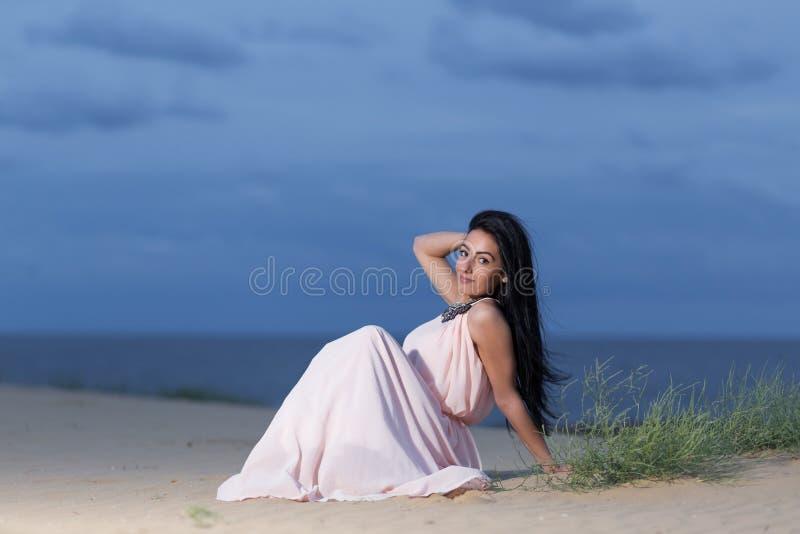 Moça com um vestido branco que senta-se em uma duna de areia fotografia de stock royalty free