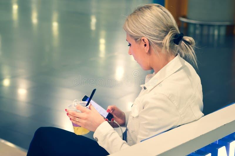 Moça com um vidro do plástico enchido com o suco, sentando-se em um terminal de aeroporto fotografia de stock