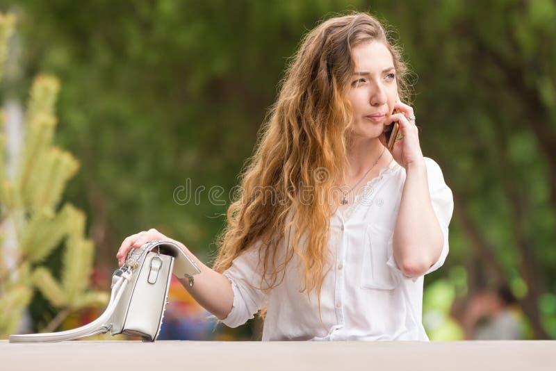 Moça com uma bolsa que fala no telefone fotos de stock