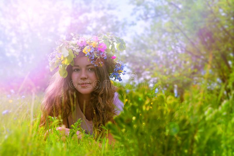 Moça com uma grinalda floral em sua cabeça na grama imagem de stock