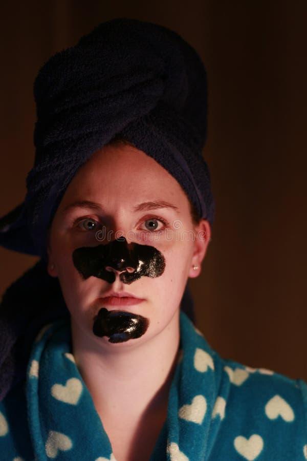 Moça 20 25 com uma máscara do carvão vegetal na cara como parte do regime da beleza após a rega imagens de stock royalty free