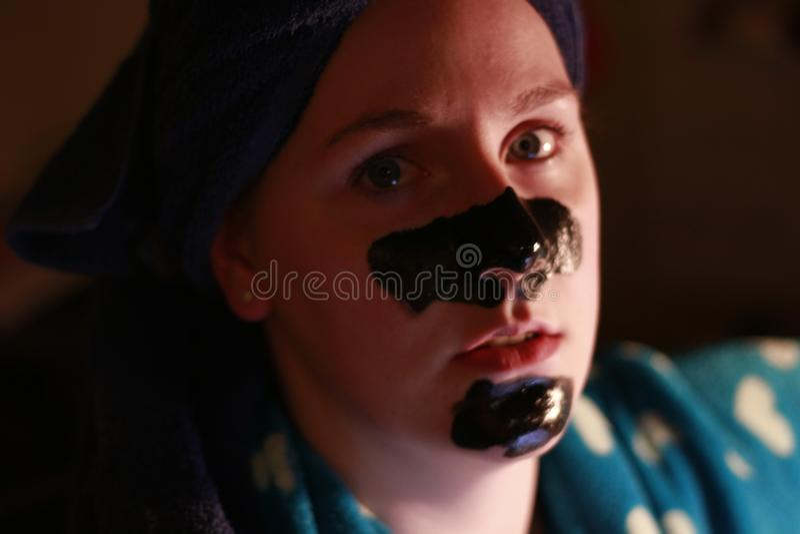 Moça 20 25 com uma máscara do carvão vegetal na cara como parte do regime da beleza após a rega imagem de stock
