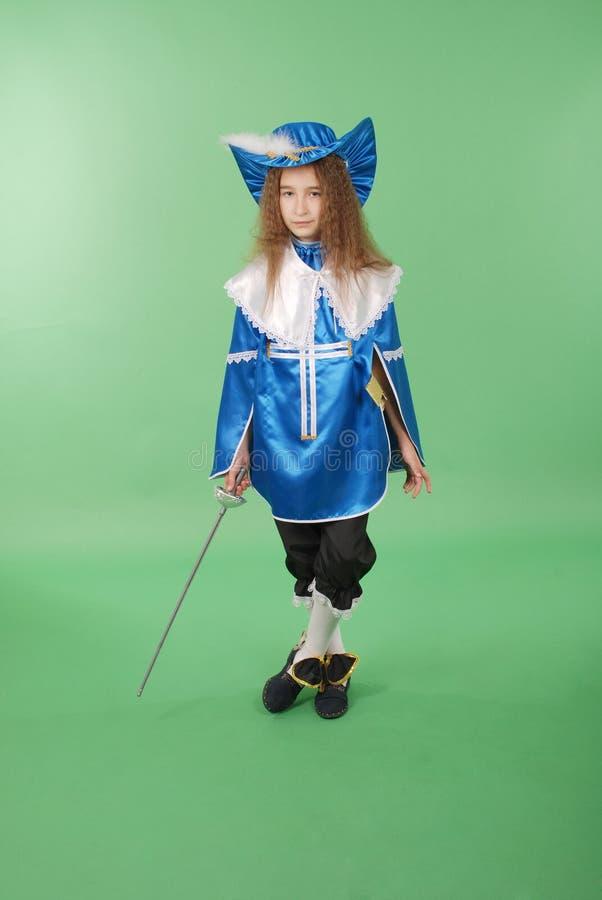 Moça como um mosqueteiro no traje azul com o chapéu azul bonito com penas foto de stock royalty free