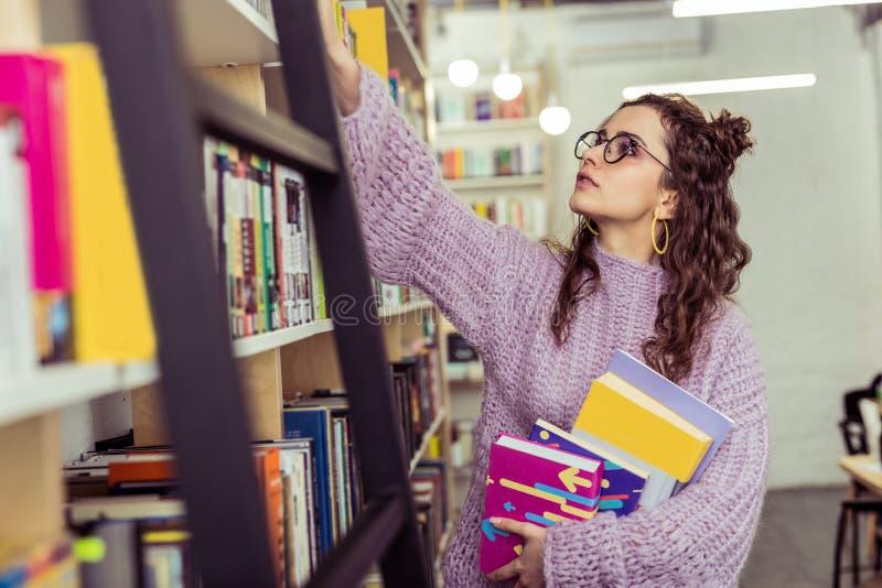 Moça curiosa na camiseta feita malha roxa que estica sua mão imagens de stock