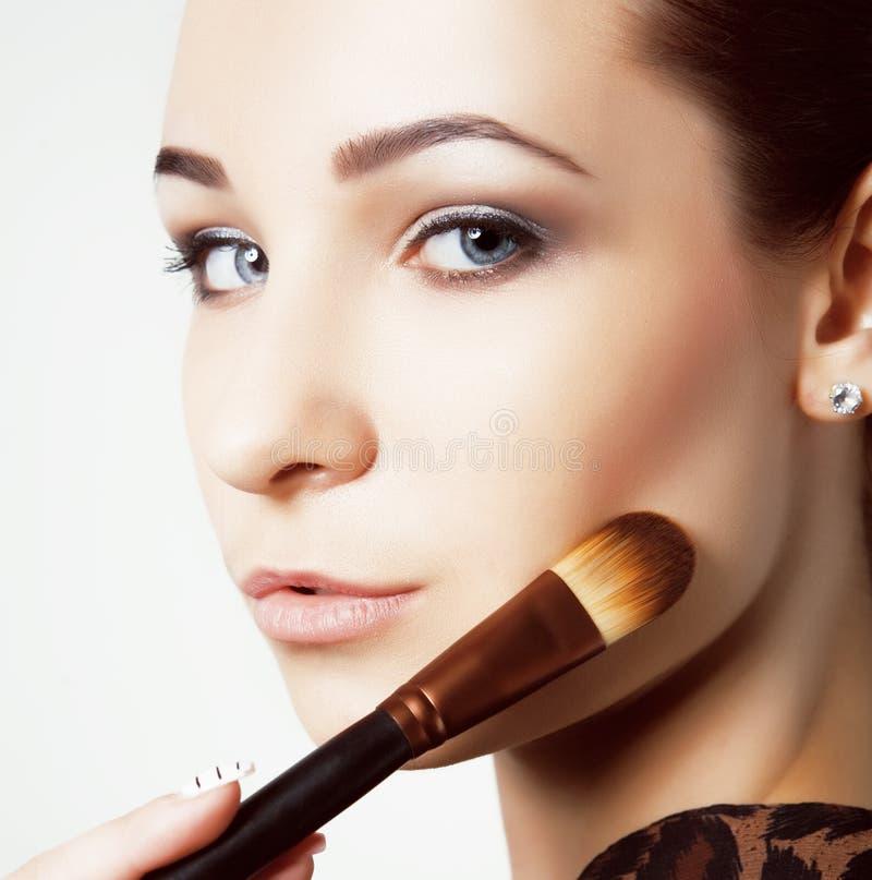 Moça da beleza com escovas da composição Natural compense pela mulher moreno com olhos do bleu Face bonita makeover Pele perfeita fotos de stock