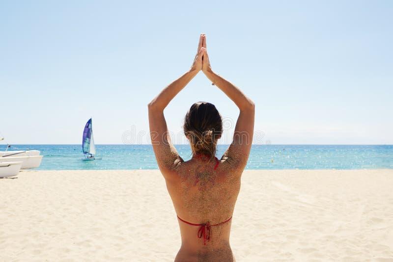 Moça da foto que faz a praia da ioga Mulher da aptidão que gasta o mar exterior do tempo ativo Oceano das Caraíbas da temporada d foto de stock