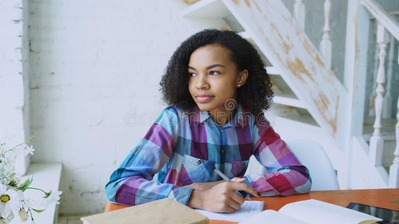 Moça de cabelo encaracolado adolescente da raça misturada que senta-se na concentração da tabela focalizada aprendendo lições par imagem de stock