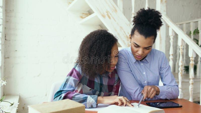 Moça de cabelo encaracolado adolescente da raça misturada que senta-se na concentração da tabela focalizada aprendendo lições e s fotos de stock
